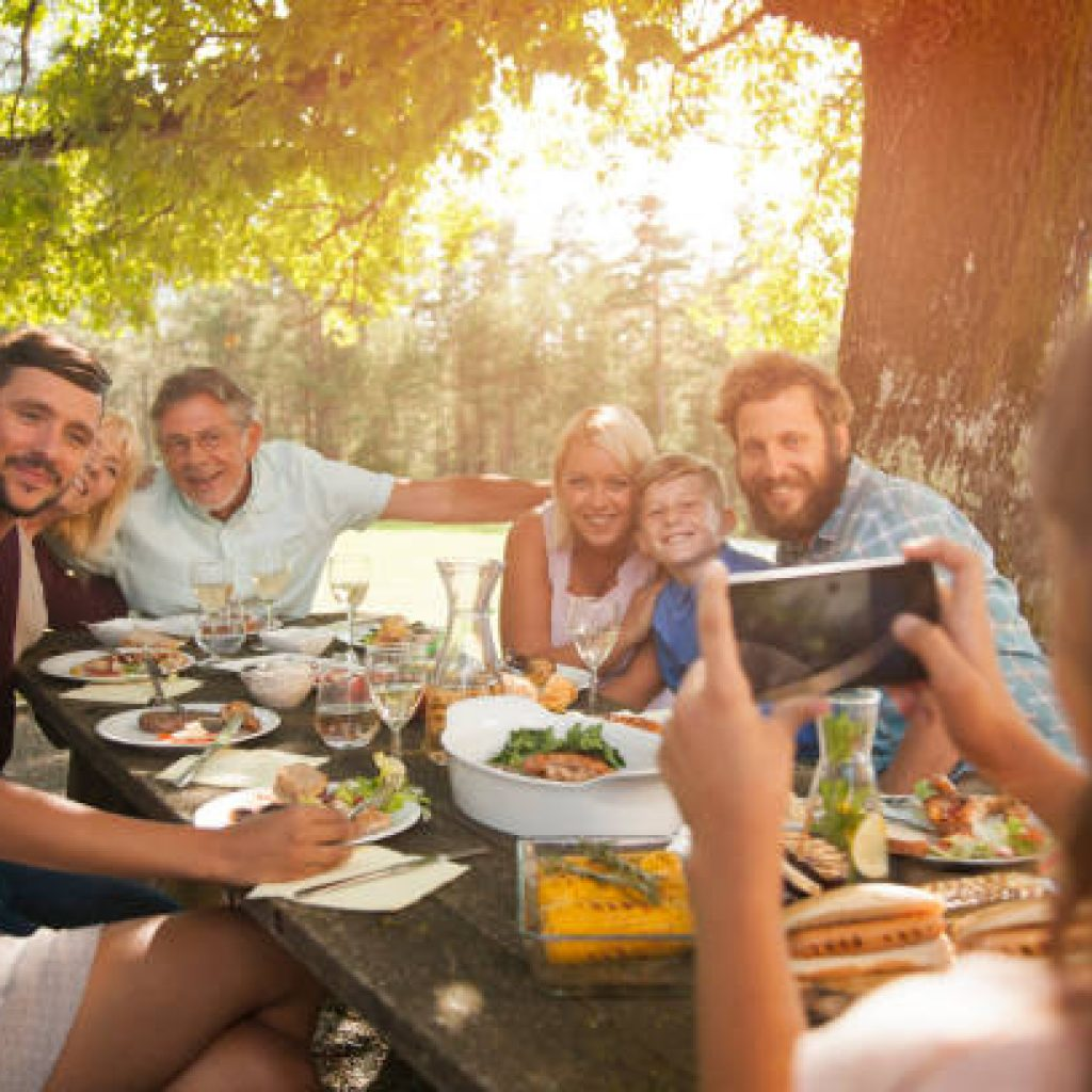 Grandfather taking a photo of his whole family on his smart phone at outdoor barbecue.