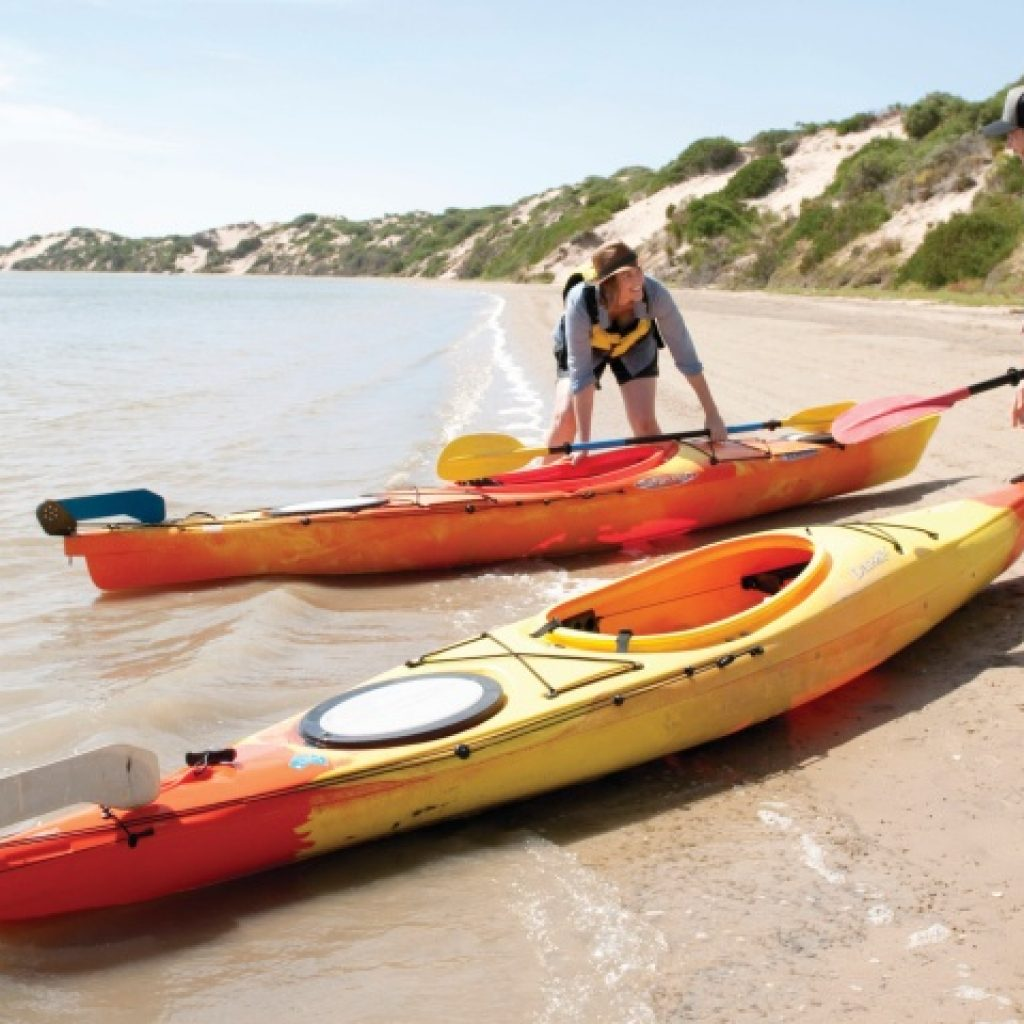 Man and woman with kayaks on beach