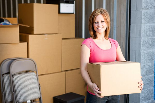 woman in a pink shirt lifting a box