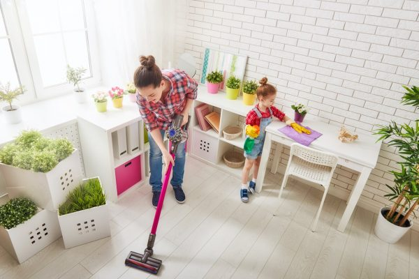 woman vacuuming the floor while girl is cleaning the table