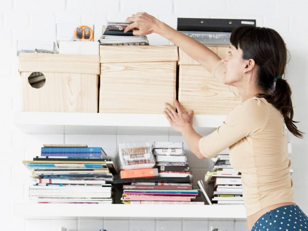 a woman reaching out to the boxes on the shelves