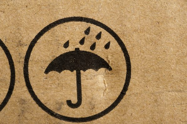 Do Not Get Wet icon stamped on brown cardboard packaging with an umbrella and shower of rain