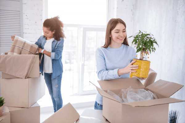 a woman placing a plant inside a cardboard box while she is packing