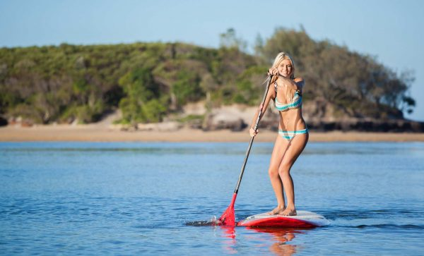 a sexy woman on her surfboard at the beach