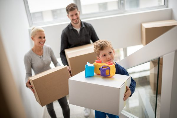young heterosexual couple with their son carrying boxes through their new apartment building.