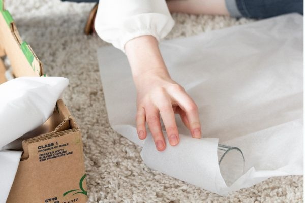 a woman wrapping a glass in packing paper for moving