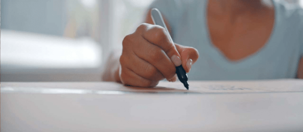 a woman using an ink pen to write