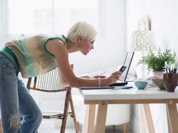 woman using a laptop while bending over