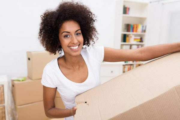 a black woman carrying a cardboard box for moving