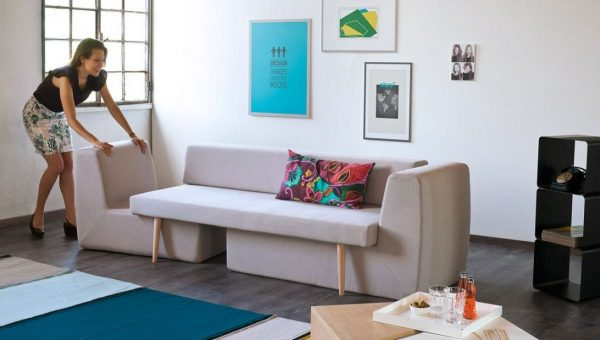 a woman tucking the chair under a sofa