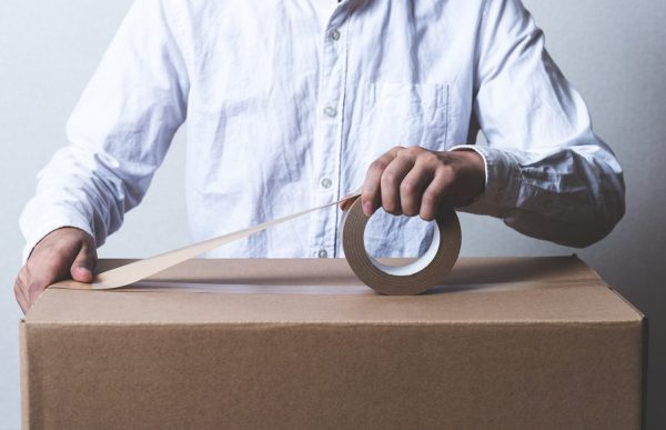 a man wrapping packing tape over a cardboard box to seal it