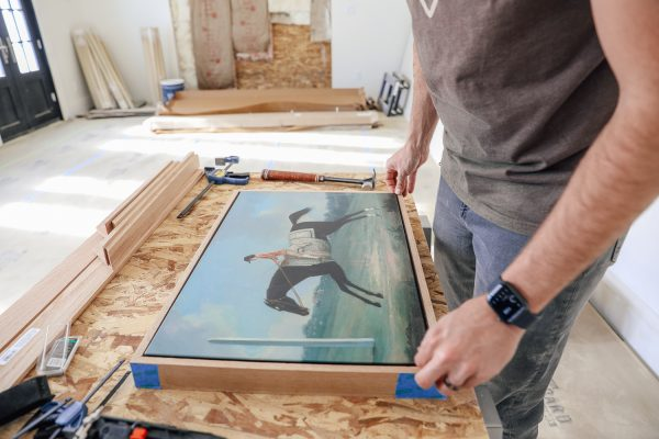 a man framing a painting of a man riding a horse