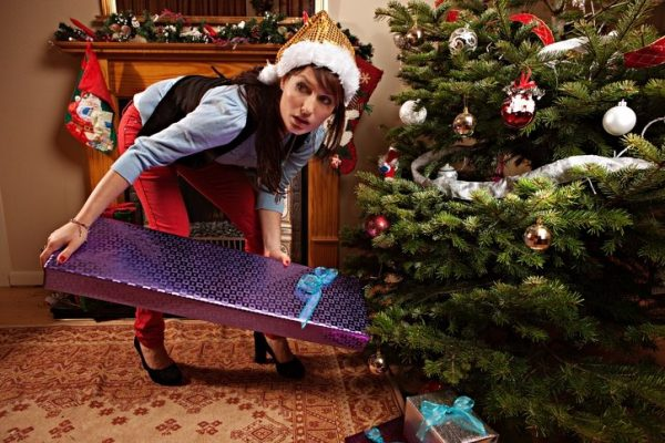 A woman hiding a gift under the Christmas tree
