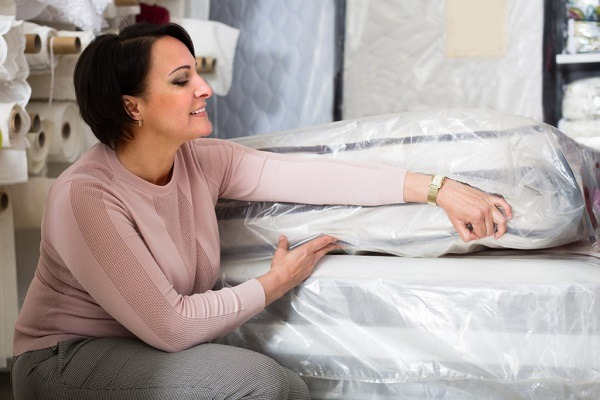 A woman wrapping mattress with a plastic cover