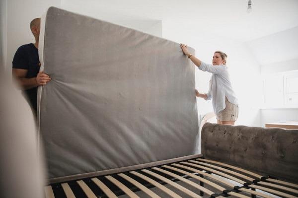 A couple moving a mattress
