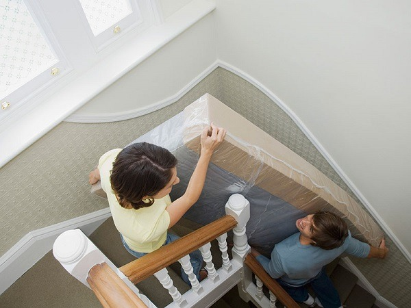 A couple moving a mattress up the stairs